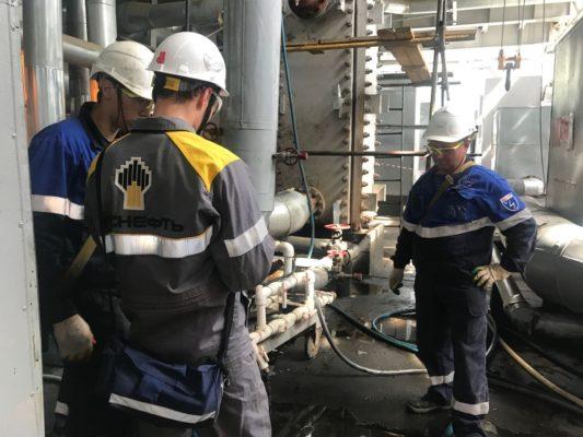 Короткое совещание специалистов в ходе очистки теплообменного оборудования